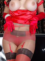 Busty lady in red wearing sexy boots, doing a leg show in red stockings worn under shiny pantyhose